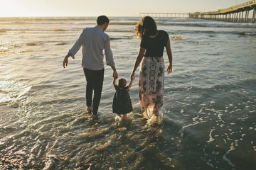 Rear view of parents holding daughter's hands while walking in sea