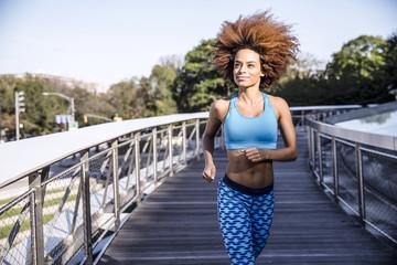 Woman jogging on bridge against sky