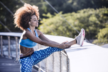 Woman stretching legs while listening music