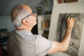 Concentrated senior man sketching on canvas at home