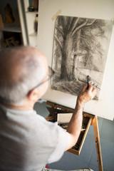Senior man sketching on canvas at home