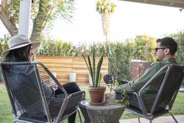Couple talking while sitting on chair in backyard