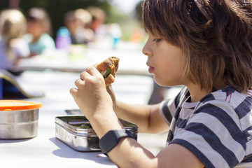 Side view of boy eating sandwich during school lunch