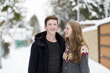 Portrait of happy teenage boy with sister standing on footpath