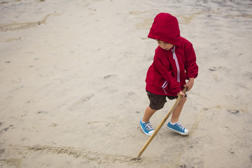 High angle view of boy drawing line on sand with stick