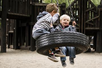Happy brothers swinging in playground