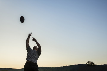 Low angle view of man playing rugby against clear sky during sunset