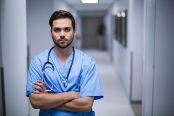 Portrait of male nurse standing in corridor