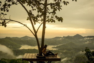 Woman relaxing while sitting on observation point during sunset