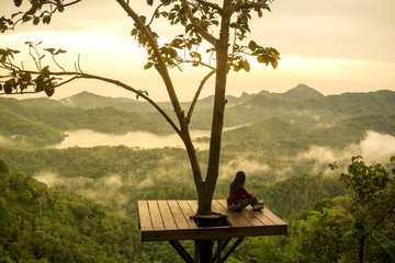 Woman sitting on observation point and looking at view