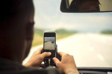 Close-up man using smartphone while sitting in car