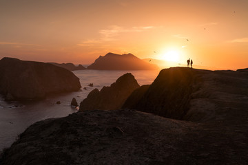 Silhouette couple standing on rock formation by sea against sky