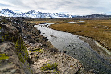 Flowing water amidst field by snowcapped mountain