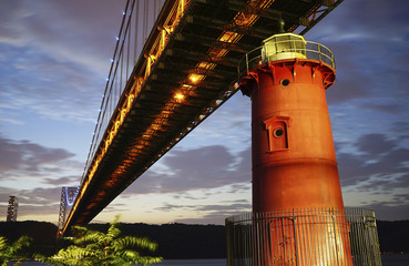 George Washington Bridge over lighthouse at dusk