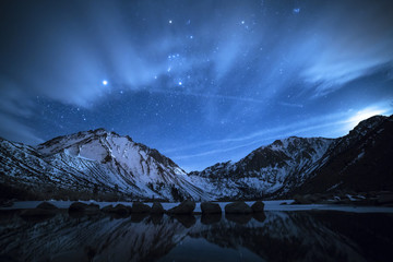 Scenic view of snow covered mountain against starry sky