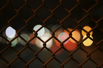 Defocused lights seen through fence at night