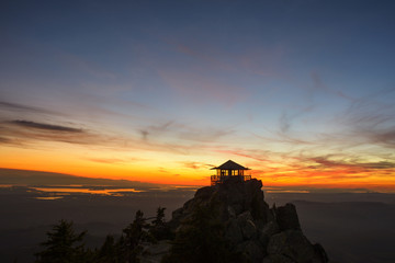 Silhouette fire lookout tower on mountains against sky during sunset