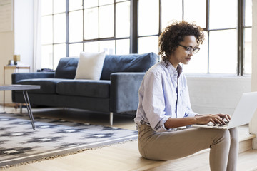 Businesswoman using laptop computer while sitting in lobby at office