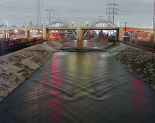 Illuminated bridge over river in city at dusk