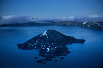 Scenic view of Wizard island in crater lake against sky at dusk
