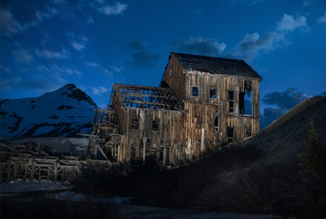 View of old abandoned wooden house against sky at dusk