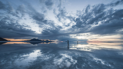 Silhouette people standing on Bonneville Salt Flats against cloudy sky