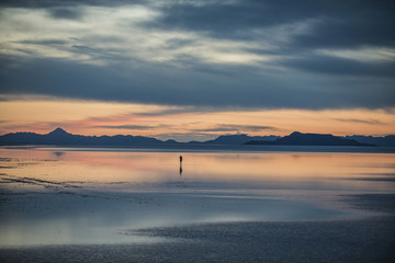 Silhouette person standing on Bonneville Salt Flats against cloudy sky