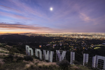 High angle view of Hollywood sign by illuminated city at dusk