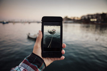 Cropped image of man photographing tied boats moored at sea