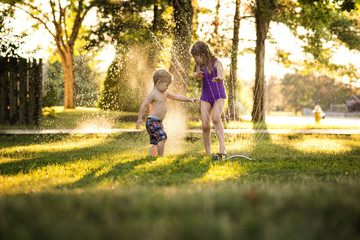 Cheerful siblings playing in sprinkler