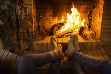 Low section of couple resting by fireplace at home