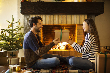 Happy couple holding Christmas present by fireplace at home
