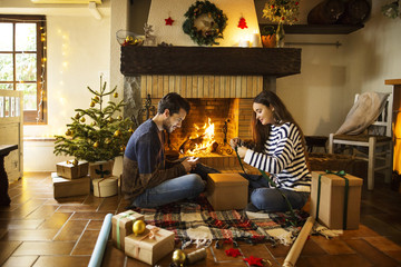 Couple wrapping gift boxes on floor by fireplace at home