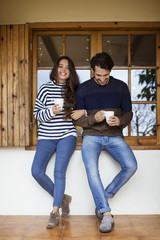 Happy couple having coffee while standing against window on porch