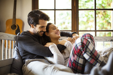 Happy loving couple leaning on alcove window seat at home