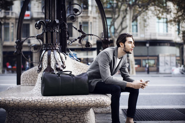 Man with mobile phone looking away while sitting on bench