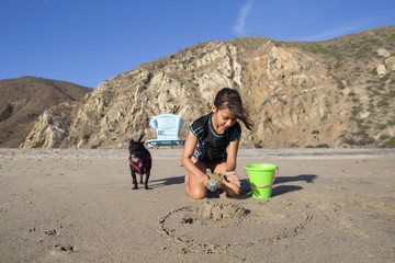 Girl playing with sand while sitting by dog at beach against mountains