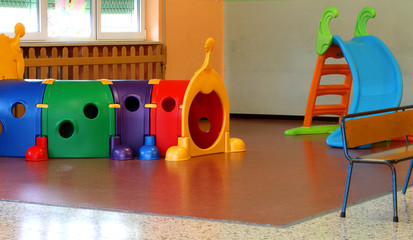 a tunnel shape game and a slide in the large hall of kindergarte
