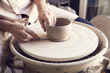 Woman molding clay on pottery wheel