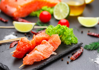 Raw salmon skewers on a stone plate. tomatoes, lime and lettuce for cooking.