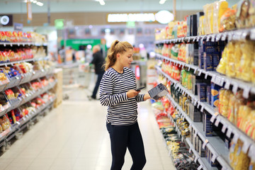 Woman shopping in supermarket reading product information.Using smarthone