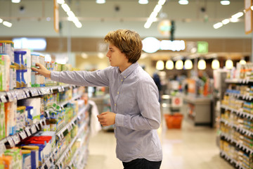 Man shopping in supermarket reading product information. Checking list.