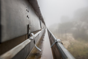 Gutter drainage system on the roof with dripping fog