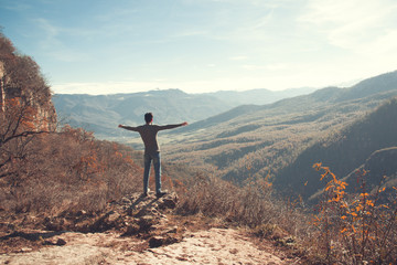 Happy young man standing with raised arms in  mountains