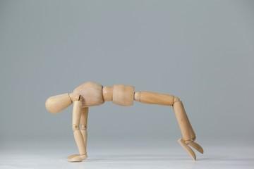 Wooden figurine exercising on floor