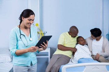 Doctor using digital tablet in front of patient