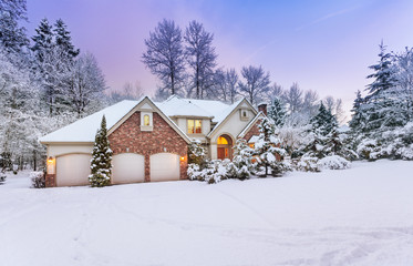 Driveway view of snowy home - daylight fades over a snow-covered suburban home