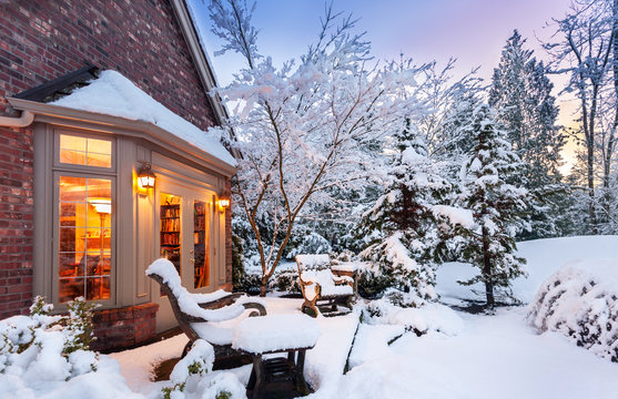 Wintry home at sunset - patio and garden blanketed in snow as sun goes down on a winter evening