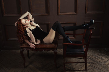 Red-haired woman covering her eyes while lying on the coffee table.