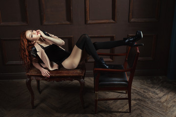 Woman lies on a table, and legs put on the leather chair.